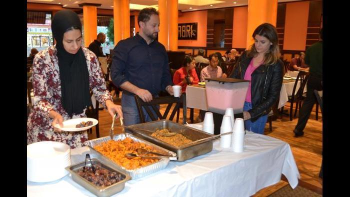 Customers at Sabri Nihari help themselves to the free buffet of dates, pakora, chickpeas and roohafza.