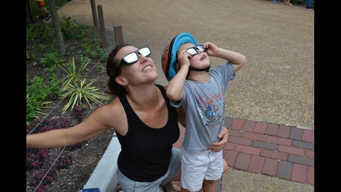 Maria Opdycke and her son try out their solar glasses at Lincoln Park Zoo. (Alex Ruppenthal / Chicago Tonight)
