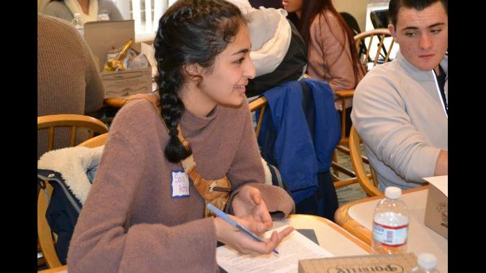 Mikva Challenge student Sara Hattab talks with her group about key points to include in a campaign public service announcement. (Kristen Thometz / Chicago Tonight)