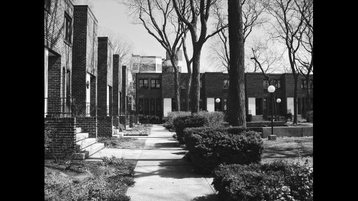 """Ezra Gordon lived in Madison Park for seven years and recalled that the community was """"badly deteriorated"""" during the years prior to urban renewal. After working for Harry Weese, he bid on sites in Hyde Park, independently and was awarded two. These compromised the Commons, a development conceived to exist in concert with the surrounding neighborhood."""