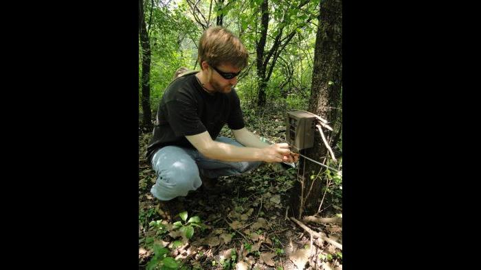 Dr. Seth Magle places a wildlife camera trap.