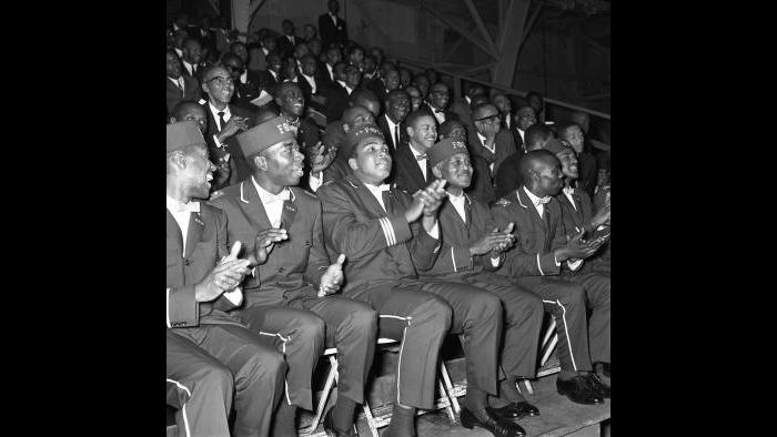 Ali cheers at a Nation of Islam rally, dressed in the uniform of the Fruit of Islam, a male-only paramilitary wing within the organization. (© Lowell K. Riley)