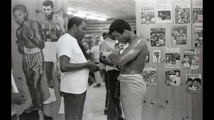 Drew Bundini Brown, Ali's friend and chief motivator, tapes the fighter's hands at their new training camp in Deer Lake, Pennsylvania. (© Kwame Brathwaite)