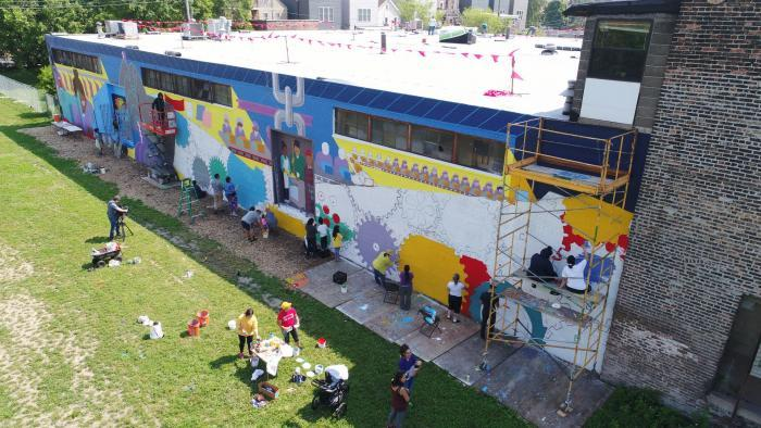 Painting the garden's El Abrazo murals was a communal project. (Courtesy of El Paseo Community Garden)