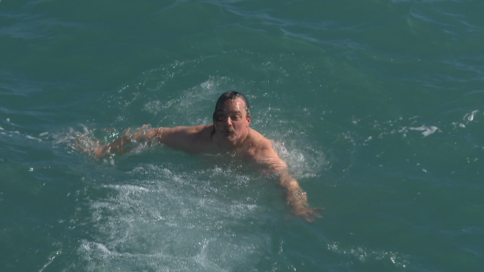 Dan O'Conor swims back to a lakefront ladder at Fullerton Beach after diving headfirst into Lake Michigan on Feb. 26, 2021. (WTTW News)