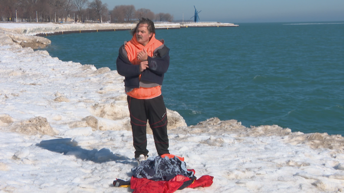 Dan O'Conor strips off his outer layer of clothing at Fullerton Beach before plunging into Lake Michigan on Feb. 26, 2021. (WTTW News)