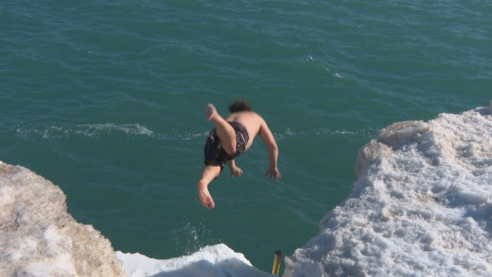 Dan O'Conor dives headfirst into Lake Michigan at Fullerton Beach on Feb. 26, 2021. O'Conor said it was his 159th consecutive day of swimming in the lake. (WTTW News)