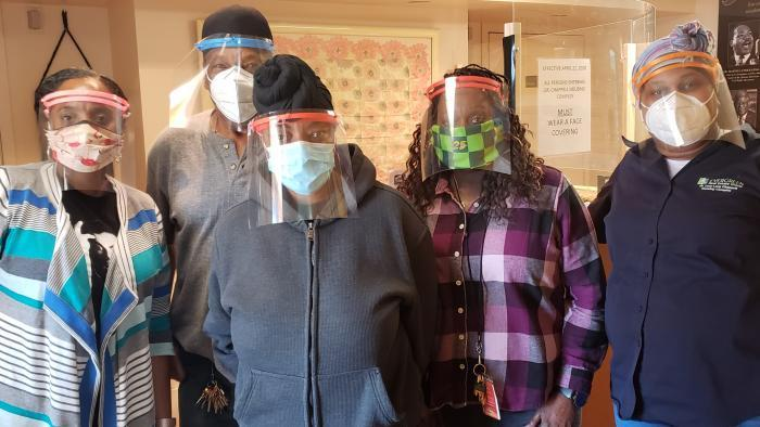 "Employees of the Dr. Lucy Lang-Chappell Housing Complex in Chicago wear face shields provided by the ""Noble Army."" (Courtesy of Rob and Susan Parks)"