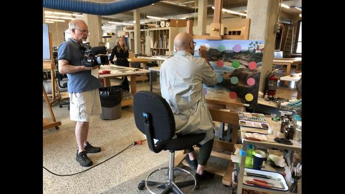 WTTW videographer Tom Siegel films the conservation treatment of a painting.