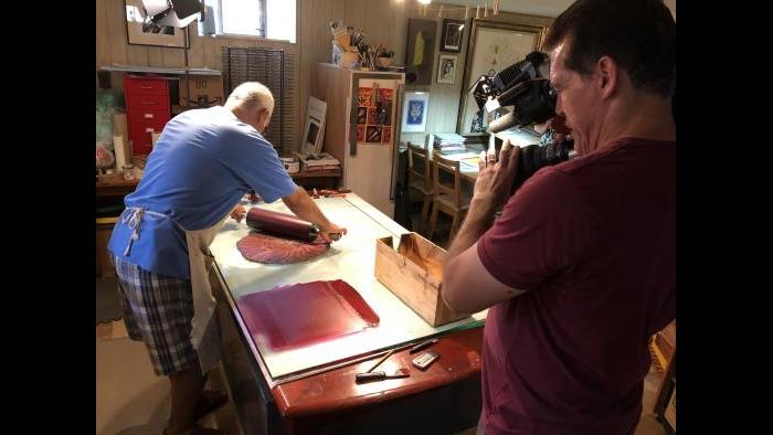 """Cameraman Felix Mendez shoots footage for this """"Chicago Tonight"""" story as artist Rene Arceo works. (Marc Vitali / WTTW News)"""
