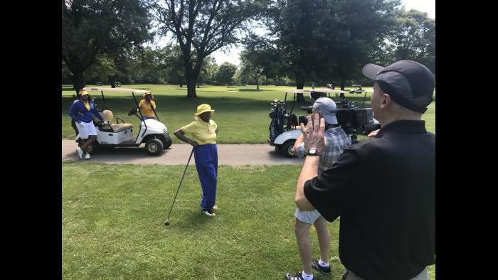 """Jay Shefsky and photographer Dave Moyer film Ernestine Harper and other members of the Chicago Women's Golf Club at Joe Louis """"The Champ"""" Golf Course in Riverdale."""