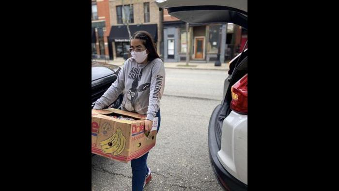 A volunteer carries a box of bananas that will be distributed to families in need through the Feed the Crib initiative. (Courtesy Elizabeth Morales)