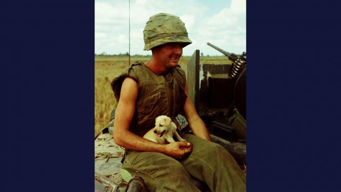 Refuge, 1966. A soldier from the U.S. Army 1st Infantry Division holds a puppy that managed to survive an air strike near Laike. Photo by Specialist 5 Robert C. Lafoon, U.S. Army.