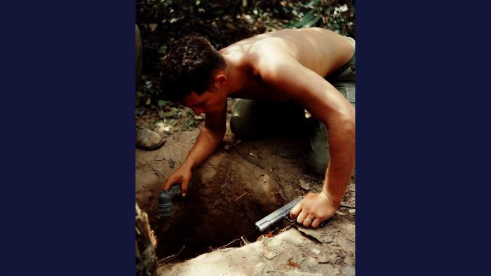Tunnel Rat, 1967. Flashlight and .45 pistol in hand, a squad leader from the U.S. Army 25th Infantry Division searches for the enemy in an underground tunnel in Củ Chi, northwest of Saigon. Photo by Specialist 5 Robert C. Lafoon, U.S. Army.