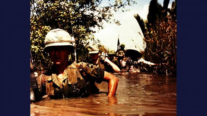 "Not a Drop to Drink, 1967. A DASPO motion picture (""mopic"") cameraman accompanies members of the U.S. Army 199th Light Infantry Brigade as they wade through a deep irrigation canal near Cát Lái. Photo by Specialist 5 Robert C. Lafoon, U.S. Army."