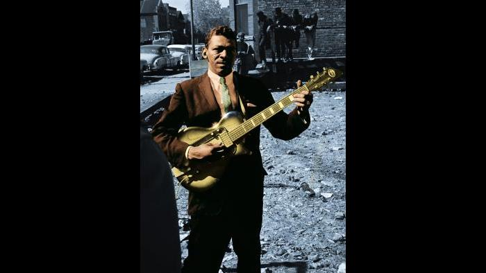 Little Walter, known for his revolutionary harmonica style, poses on Maxwell Street with his guitar in 1963. Raeburn Flerlage image, colorized.