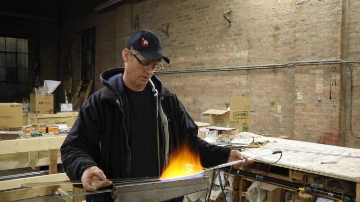 Neon Design owner Charles Evanson bends glass in Rogers Park.