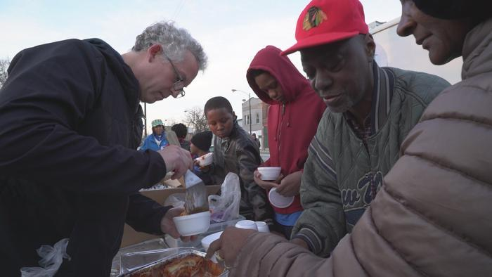 A Night Ministry volunteer serves lasagna to members of the Back of the Yards community. (Chicago Tonight)