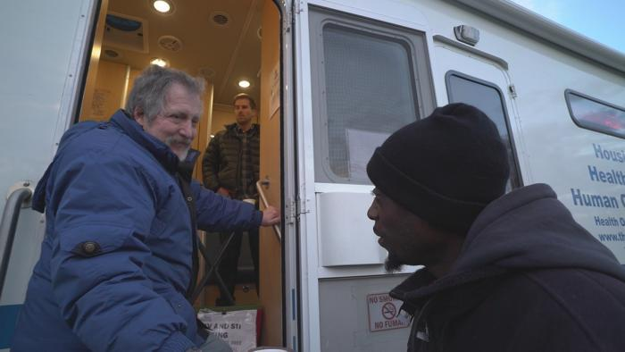 Volunteer Jim Lacy speaks with a man at the Night Ministry's outreach bus. (Chicago Tonight)