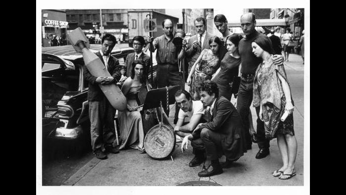 Peter Moore. Publicity photograph for 3rd Annual New York Avant Garde Festival, August 26, 1965. Left to right: Nam June Paik, Charlotte Moorman, Takehisa Kosugi, Gary Harris, Dick Higgins, Judith Kuemmerle, Kenneth King, Meredith Monk, Al Kurchin, Phoebe Neville. In front, kneeling, Philip Corner and James Tenney. (Photograph © Barbara Moore/Licensed by VAGA, NY.)