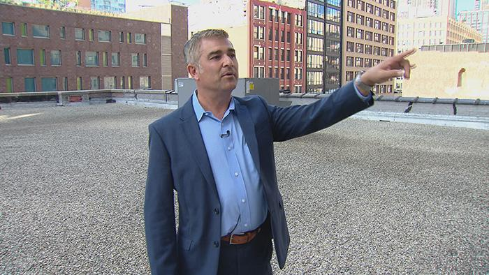 Ed Rossini on the roof of Palmer Printing, pointing to the business' former location on Federal Street.