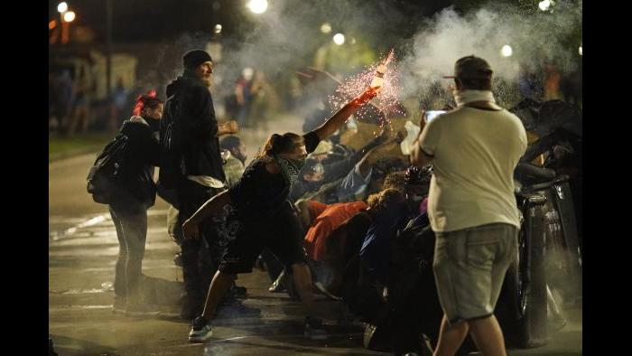 A protester tosses an object toward police during clashes outside the Kenosha County Courthouse late Tuesday, Aug. 25, 2020, in Kenosha, Wis. (AP Photo / David Goldman)