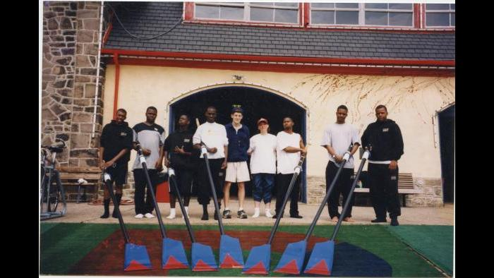The Manley Crew in front of a boathouse. © 1999 Marc Mandel Courtesy of 50 Eggs Films
