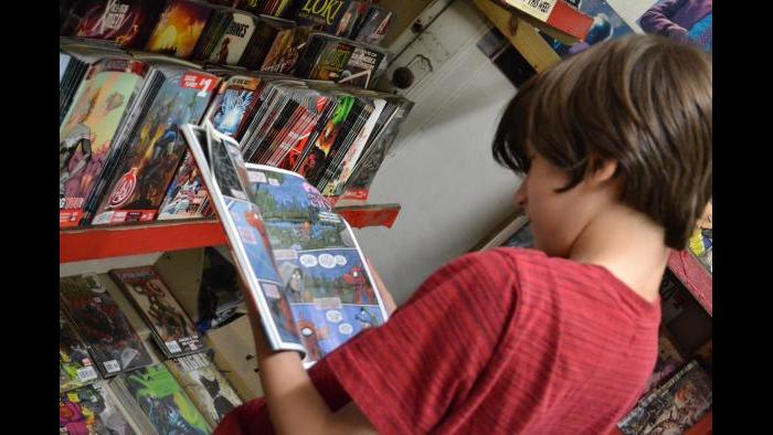 West Rogers Park resident Julian Kane looks at a Spiderman comic book. (Photo/Kristen Thometz)