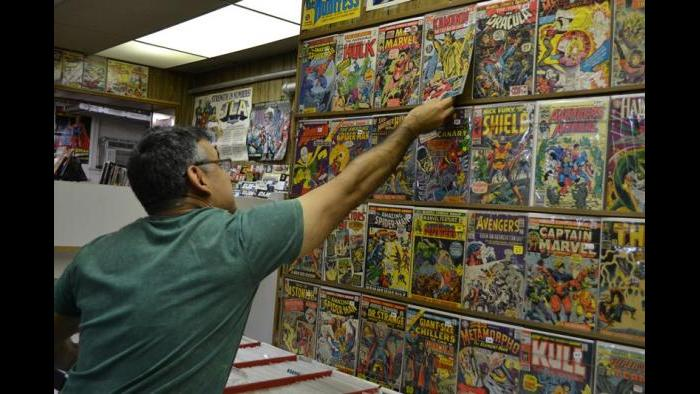 Variety Comics co-owner Victor Olivarez adjusts a comic displayed on the store's wall. (Photo/Kristen Thometz)