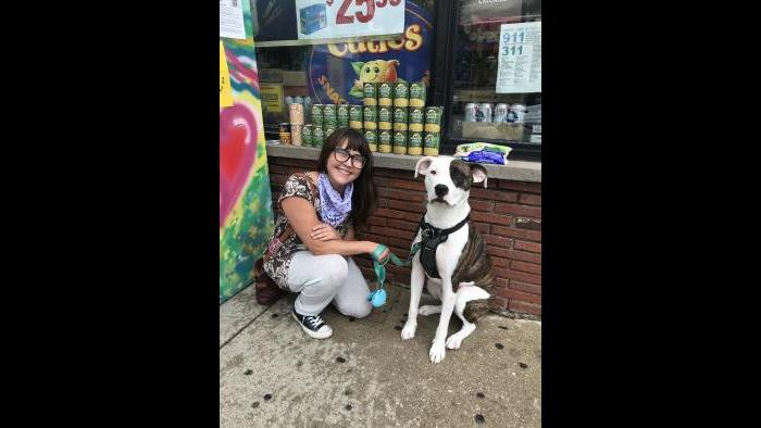 Allie Mae Miller and her dog, Abe, sit next to the refrigerator she painted and donated to the Love Fridge project in Avondale. (Ariel Parrella-Aureli / WTTW News)
