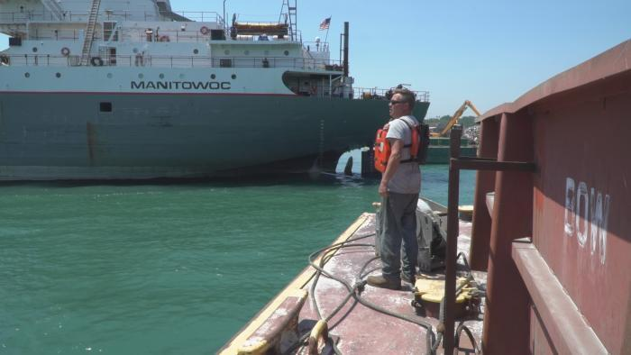 Deckhand Bill Hruska, at the front of the barge, giving signals to Captain Van Dusen.