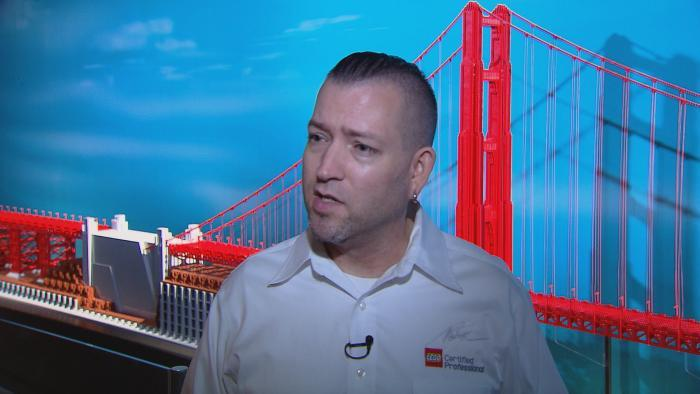 Tucker stands in front of his model of the Golden Gate Bridge.