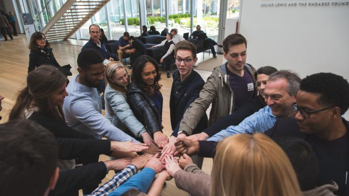 """Each museum hack tour begins with the group huddling together and putting their hands down on """"muse"""" and their hands up on """"eum,"""" says Michael Alexis. (Courtesy of Museum Hack)"""