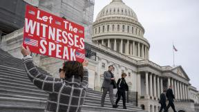 Laura Albinson of Pasadena, Md., displays a message for members of the House as they leave the Capitol in Washington, Friday, Jan. 10, 2020. (AP Photo / J. Scott Applewhite)