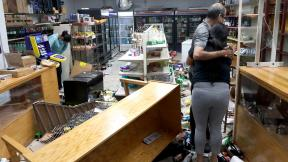 Yogi Dalal hugs his daughter Jigisha Monday, Aug. 10, 2020, after she arrived at the family food and liquor store and as his other daughter Kajal, left, bows her head after the family business was vandalized in downtown Chicago. (AP Photo / Charles Rex Arbogast)