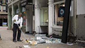 A man sweeps up outside Paul Young Fine Jewelers after looting broke out in the Loop and surrounding neighborhoods overnight, Monday morning, Aug. 10, 2020 in Chicago. (Ashlee Rezin Garcia / Chicago Sun-Times via AP)