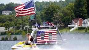 A jet skier passes a patriotic shanty-boat owned by AJ Crea on Pontoosuc Lake on Labor Day in Pittsfield, Mass., Monday, Sept. 7, 2020. (Ben Garver / The Berkshire Eagle via AP)