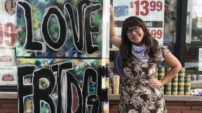 Allie Mae Miller stands next to the refrigerator she painted and donated to the Love Fridge project in Avondale. (Ariel Parrella-Aureli / WTTW News)