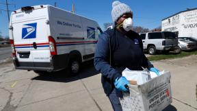 In this April 2, 2020 file photo, a United States Postal Service worker makes a delivery with gloves and a mask in Warren, Mich. I(AP Photo / Paul Sancya, File)