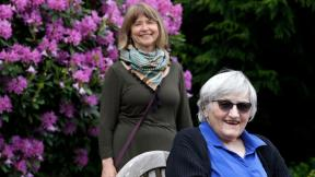 Jessie Cornwell, a resident of the Ida Culver House Ravenna, right, poses for a photo with the Rev. Jane Pauw, in Seattle on May 21, 2020. Cornwell tested positive for the coronavirus but never became ill, and may have been infectious when she shared a ride to Bible study with Pauw, who later got sick with COVID-19. (AP Photo / Elaine Thompson)