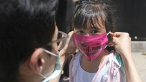 In this June 10, 2020, file photo, Olivia Chan's father helps her with a new mask she received during a graduation ceremony for her Pre-K class in front of Bradford School in Jersey City, N.J. (AP Photo / Seth Wenig, File)