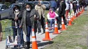 In this Tuesday, May 12, 2020, photo, residents from all walks of life line up for a food giveaway sponsored by the Greater Chicago Food Depository in the Auburn Gresham neighborhood of Chicago. (AP Photo / Charles Rex Arbogast)