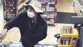 This March 26, 2020 image from surveillance video shows a man, believed to be William Rosario Lopez wearing a surgical mask, with a gun in a Connecticut convenience store. Reports are starting to pop up across the country, as well as in other parts of the world of crimes that were pulled off in no small part because so many of us are wearing masks. (U.S. District Court of Connecticut via AP)